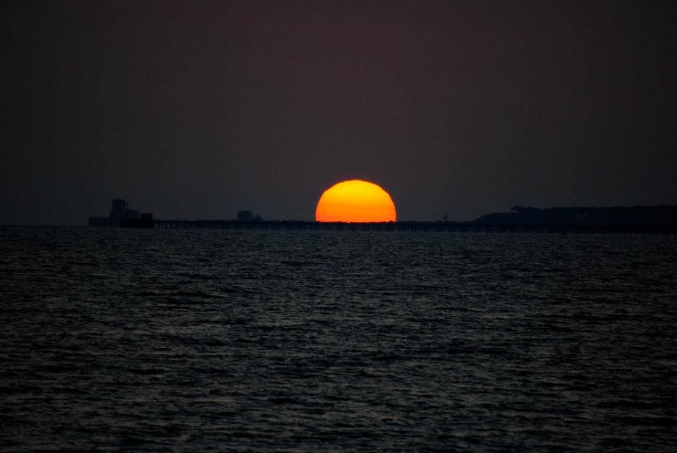 foto al tramonto in Tramonto con sole arancione perfetto sul mare a Latina