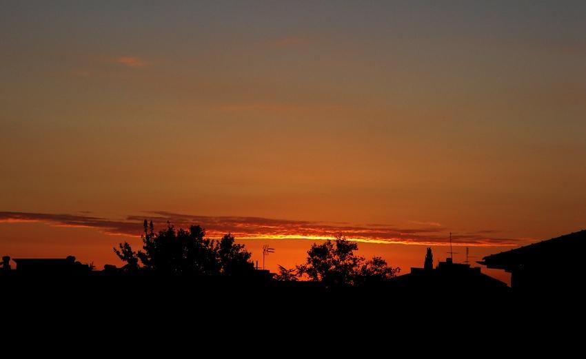 un tramonto sotto la riga in città foto di tramonti cittadino tra le case immagini al tramonto