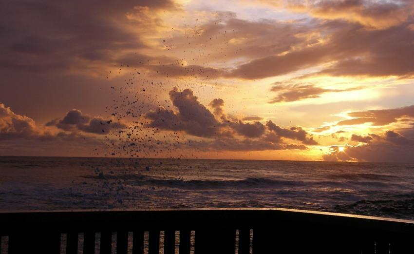 tramonto sul mare tra scogli e spruzzi a Latina Lido foto di tramonti Capoportiere nuovle sole onde spiaggia fogliano