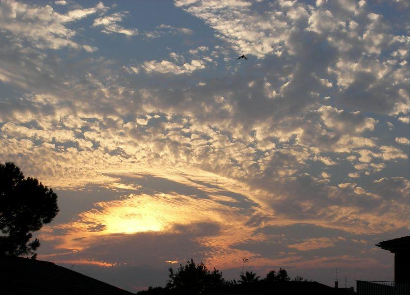 particolare di un tramonto cittadino, il sole viene nascosto da un vortice di nuvole